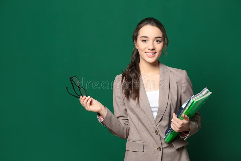 Portrait de beau jeune professeur avec des livres près du tableau, l'espace pour image libre de droits