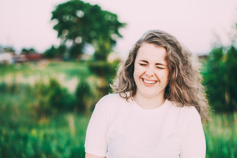 Portrait de beau plus la jeune femme de taille dans la chemise blanche posant dans le pré de champ d'été au fond de coucher du so image stock