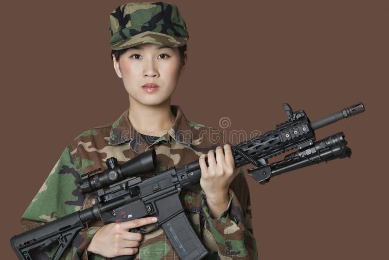 Portrait de beau soldat des USA Marine Corps de jeunes avec le fusil d'assaut M4 au-dessus du fond brun images stock