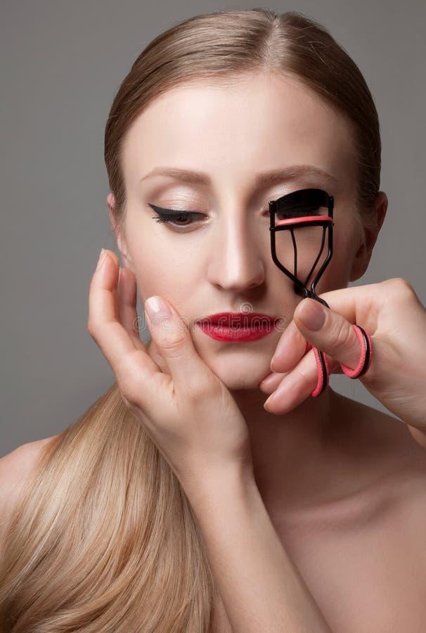 Portrait de beauté, femme faisant des cils de boucle Beau visage, maquillage parfait photos stock