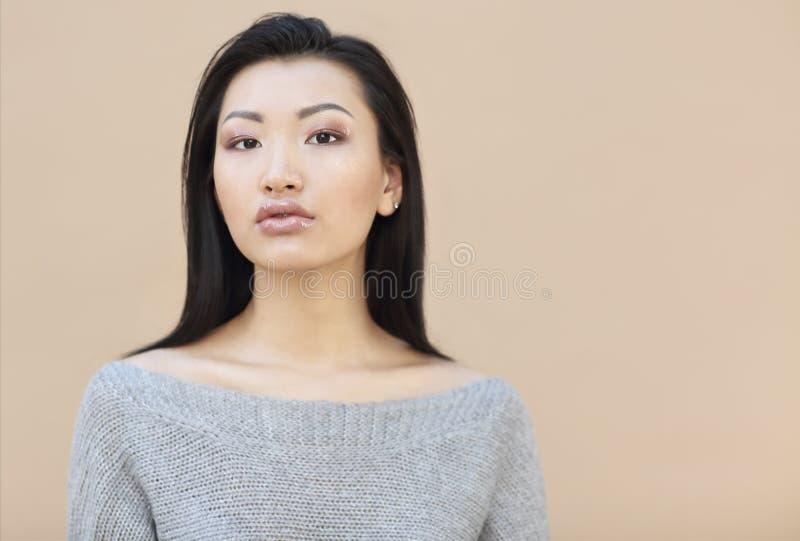 Portrait de beaut? de jeune femme asiatique sensuelle avec de longs cheveux fonc?s dans le chandail gris tricot? confortable sur  photographie stock libre de droits