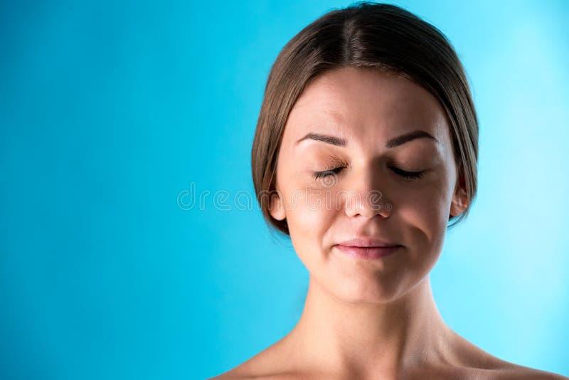 Portrait de beauté de jeune joli modèle avec le maquillage professionnel Peau fraîche et propre Yeux fermés, brune sur le bleu image libre de droits