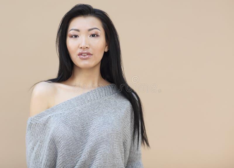 Portrait de beaut? de jeune femme asiatique sensuelle avec de longs cheveux fonc?s dans le chandail gris tricot? confortable sur  photo libre de droits