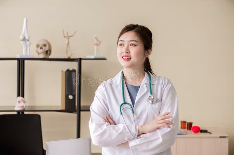 Portrait de beaux bras debout et croisés asiatiques de sourire de docteur de femme à l'attitude d'hôpital, heureuse et positive image libre de droits