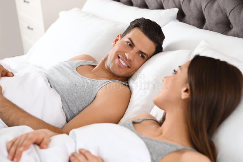 Portrait de beaux couples se reposant dans le lit confortable photo libre de droits