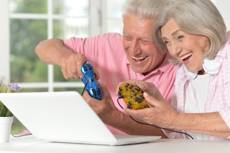 Portrait de beaux couples supérieurs heureux jouant le jeu d'ordinateur photo stock