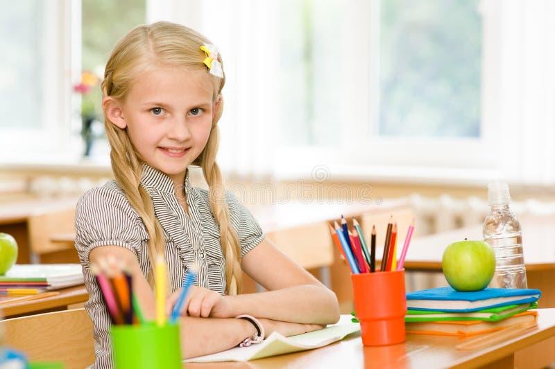 Portrait de belle écolière dans la salle de classe regarder l'appareil-photo photos stock