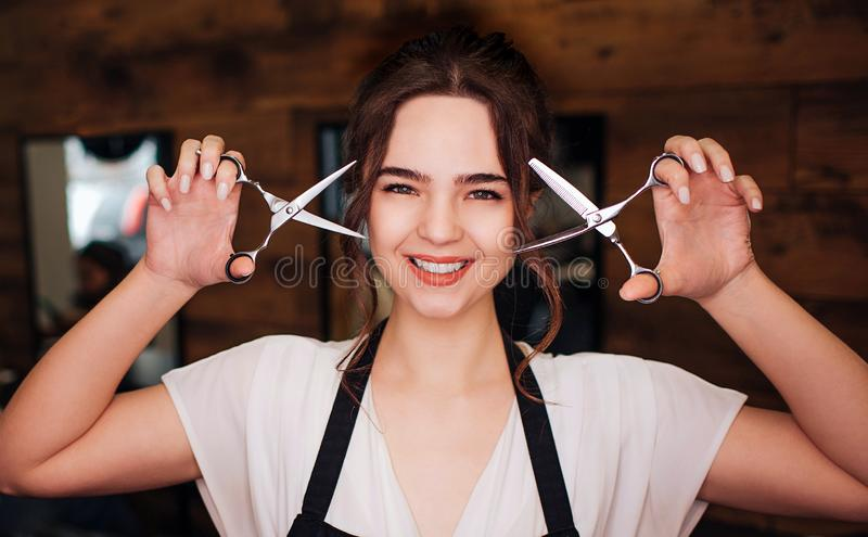 Portrait de belle coiffeuse de sourire de femme avec le tablier noir regardant la caméra tout en tenant des ciseaux professionnel photo libre de droits