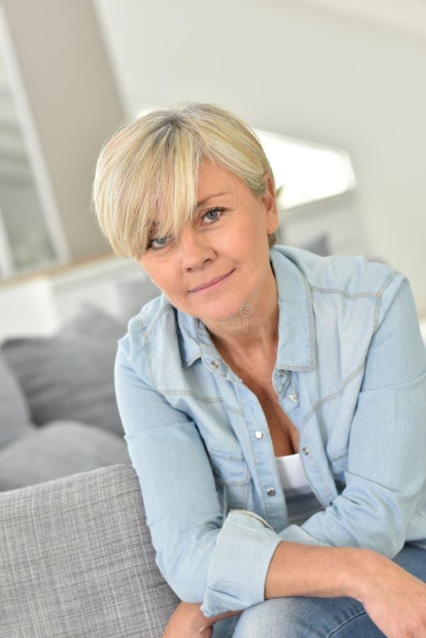 Portrait de belle dame supérieure blonde à la maison photos stock