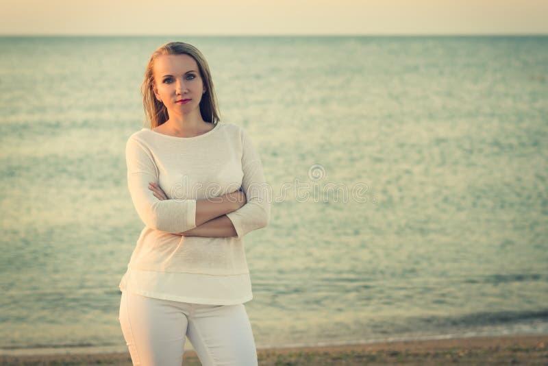 Portrait de belle femme au coucher du soleil sur la côte images stock