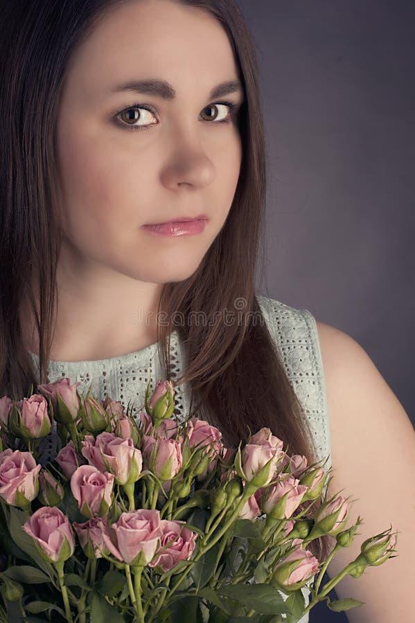 Portrait de belle femme avec du charme de brune avec les fleurs roses Photo de mode photographie stock libre de droits