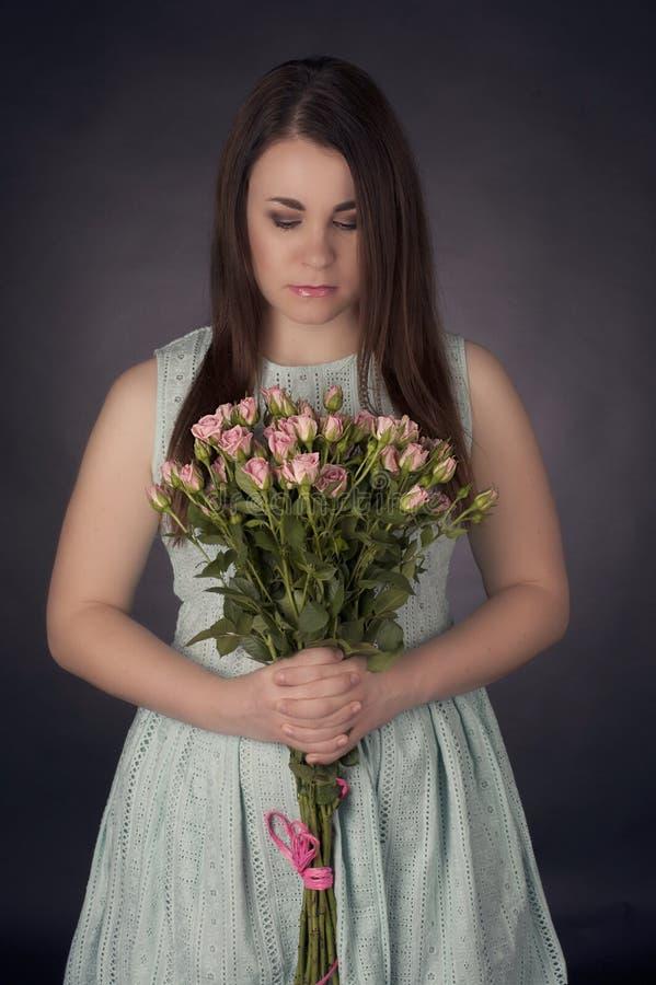Portrait de belle femme avec du charme de brune avec les fleurs roses Photo de mode image libre de droits