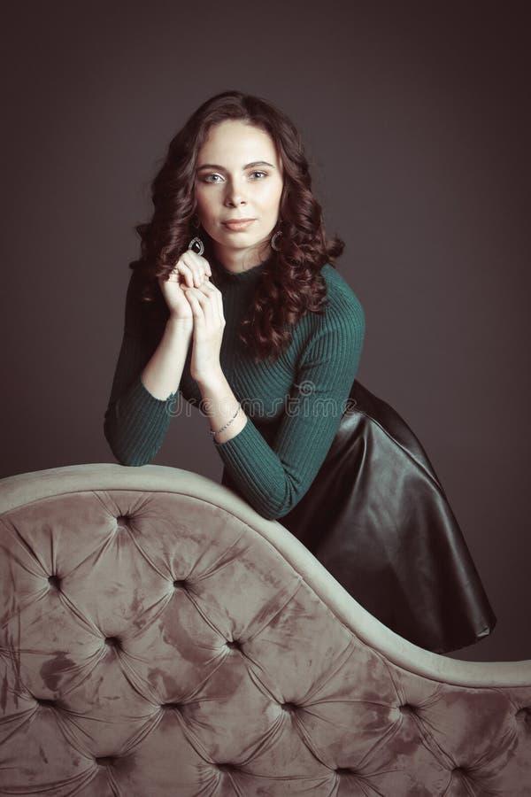 Portrait de belle femme avec le maquillage, sur un sofa, dans le chandail vert et la jupe en cuir noire posant sur le fond foncé  images stock