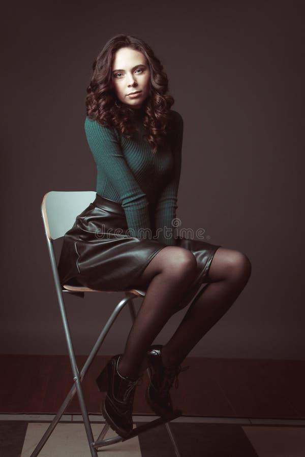 Portrait de belle femme avec le maquillage, sur une chaise, dans le chandail vert et la jupe en cuir noire posant sur le fond fon image stock