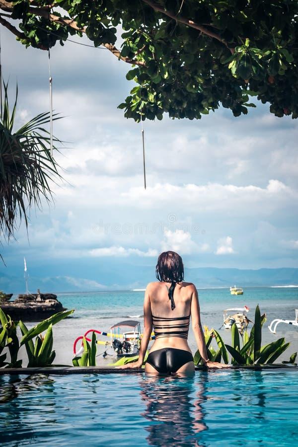 Portrait de belle femme bronzée dans des vêtements de bain noirs détendant dans la station thermale de piscine Jour d'été chaud e image stock