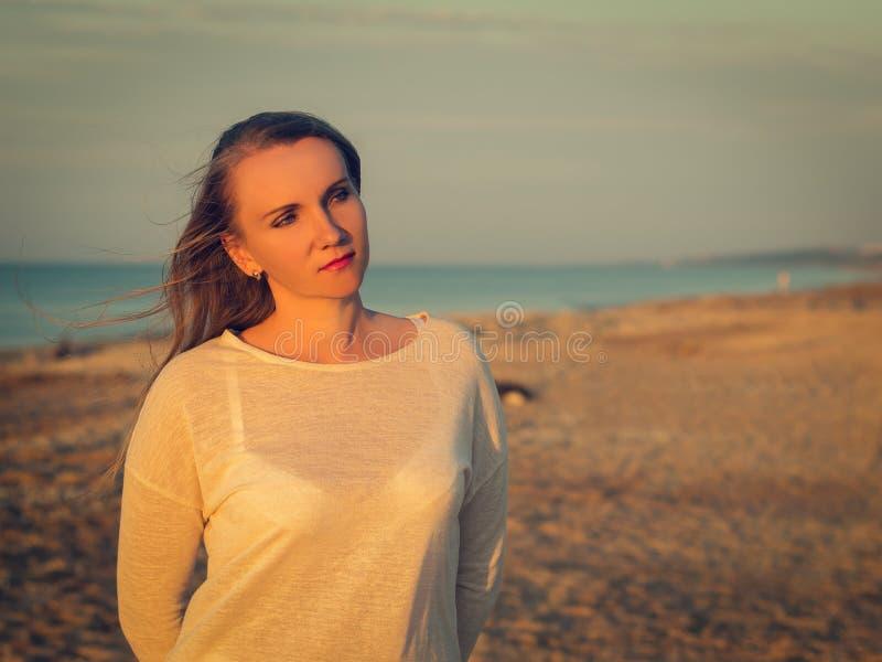 Portrait de belle femme dans des vêtements blancs sur la plage image stock