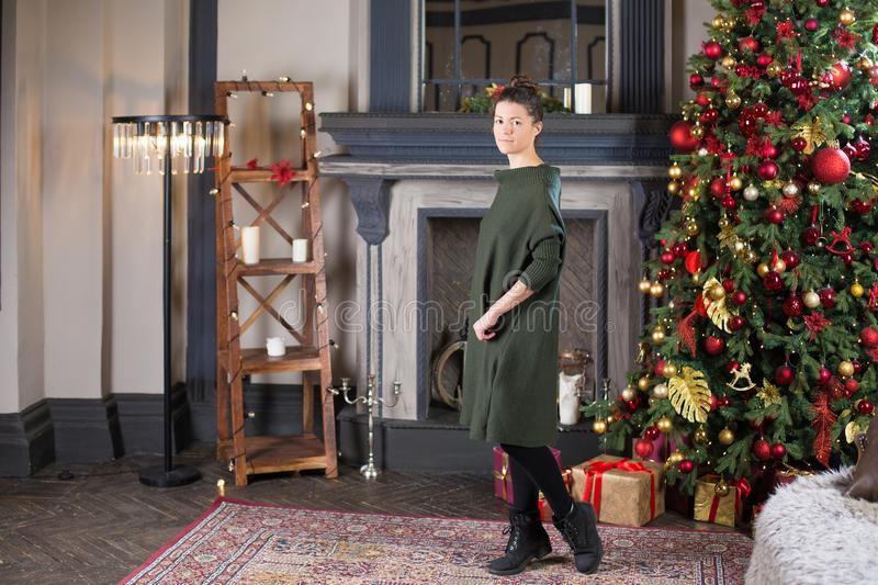 Portrait de belle femme dans la robe verte de laine contre le christm photographie stock libre de droits