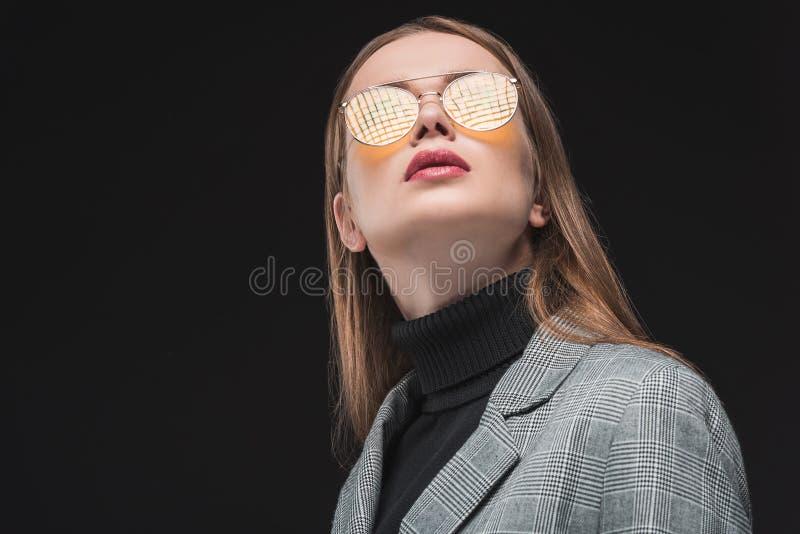 Portrait de belle femme dans la veste grise et des lunettes de soleil jaunes recherchant photo libre de droits