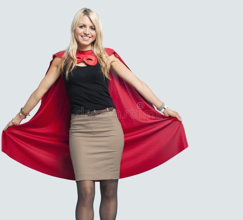 Portrait de belle femme dans le costume de super héros au-dessus du fond bleu-clair images stock
