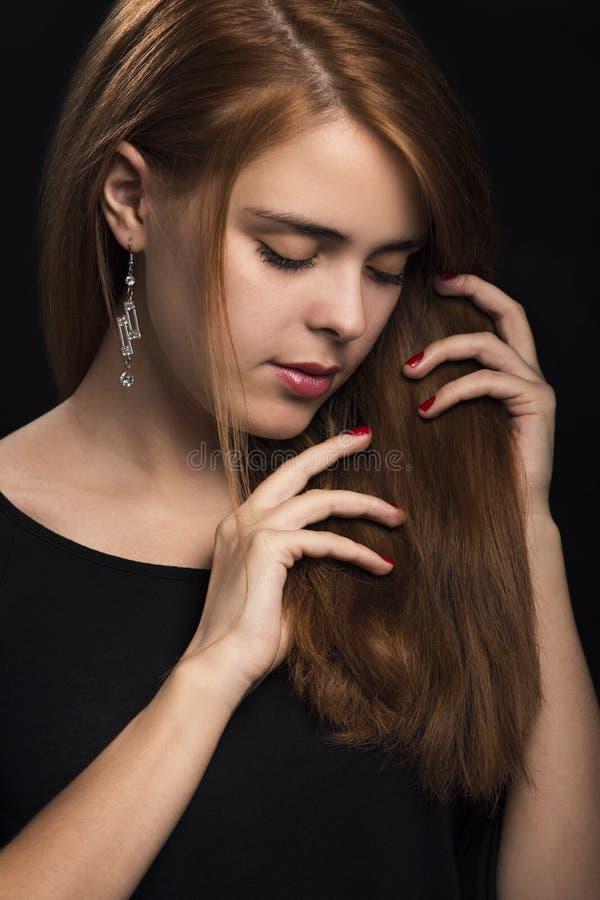 Portrait de belle femme de mode avec de longs cheveux rouges sur un fond noir photo stock