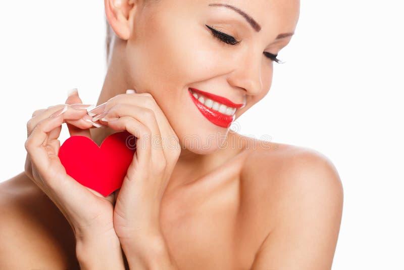 Portrait de belle femme de sourire magnifique avec le maquillage lumineux de charme et le coeur rouge à disposition image stock