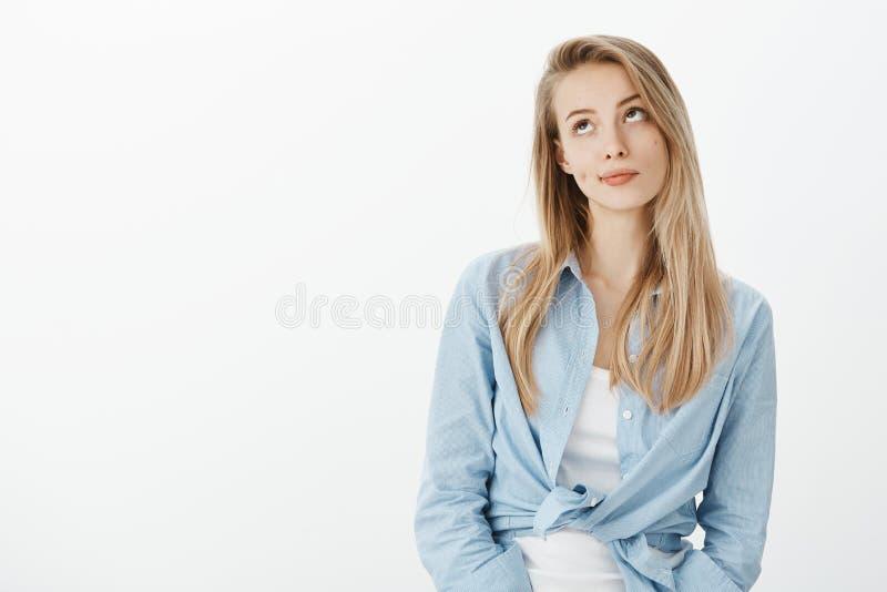 Portrait de belle femme européenne détachée avec les cheveux blonds, souriant d'un air affecté et regardant vers le haut avec ind images stock
