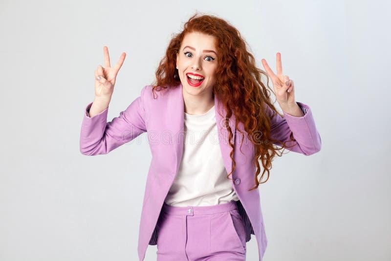 Portrait de belle femme heureuse réussie d'affaires avec les cheveux rouge-brun et de maquillage dans le costume rose montrant le images libres de droits