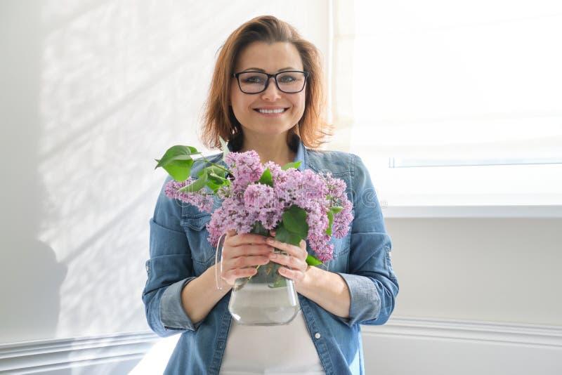 Portrait de belle femme m?re ? la maison avec le bouquet des fleurs lilas Fond de diner int?rieur ? la maison pr?s de la fen?tre photographie stock