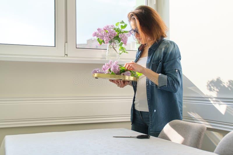 Portrait de belle femme m?re ? la maison avec le bouquet des fleurs lilas Fond de diner int?rieur ? la maison pr?s de la fen?tre photo stock