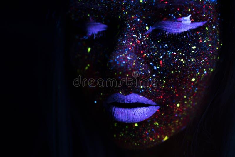 Portrait de belle femme de mode dans la lumière au néon d'uF Girl modèle avec le maquillage psychédélique créatif fluorescent, ar photos stock