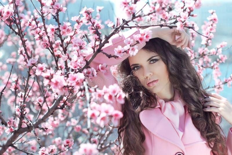Portrait de belle femme posant au-dessus des bloss roses de cerise de ressort image stock