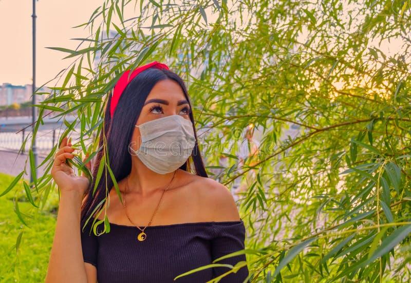 Portrait de belle femme posant dans le masque de port de grippe de parc comme protection contre des maladies infectieuses attraya photographie stock