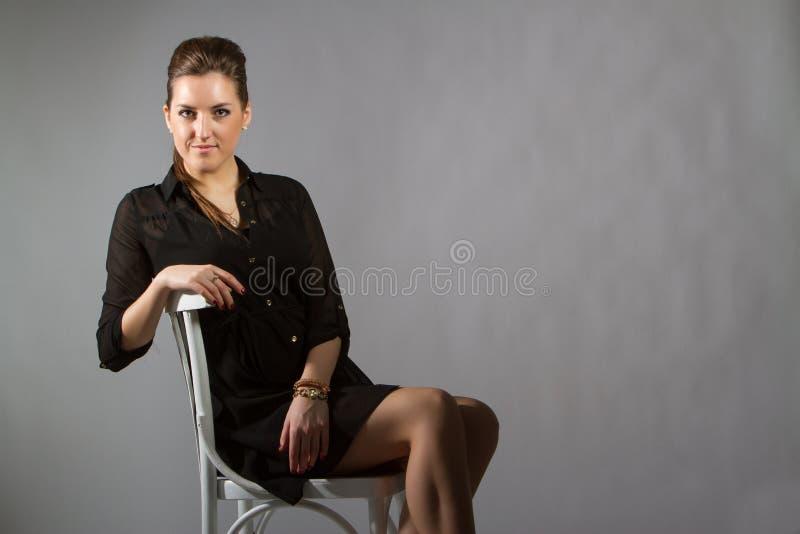 Portrait de belle femme posant dans le studio sur chear photographie stock libre de droits