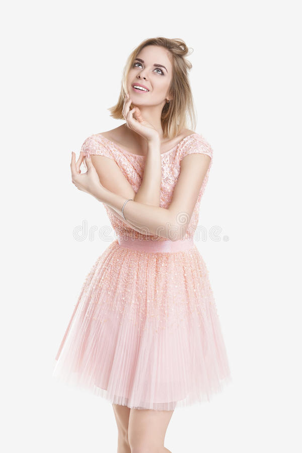 Portrait de belle femme rêveuse blonde dans la robe de cocktail rose sur le fond gris photographie stock