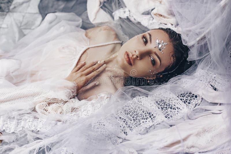 Portrait de belle femme se situant dans l'eau avec le tissu Mode photos stock