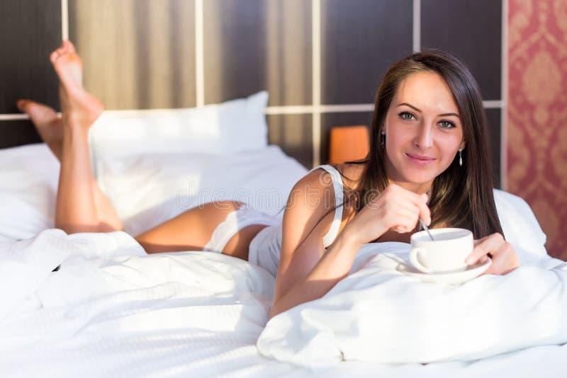 Portrait de belle femme se situant dans le lit, café potable, tenant la tasse blanche image libre de droits