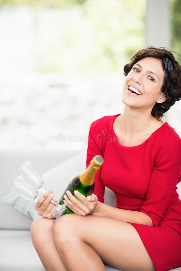 Portrait de belle femme tenant la bouteille et le verre de champagne photo stock