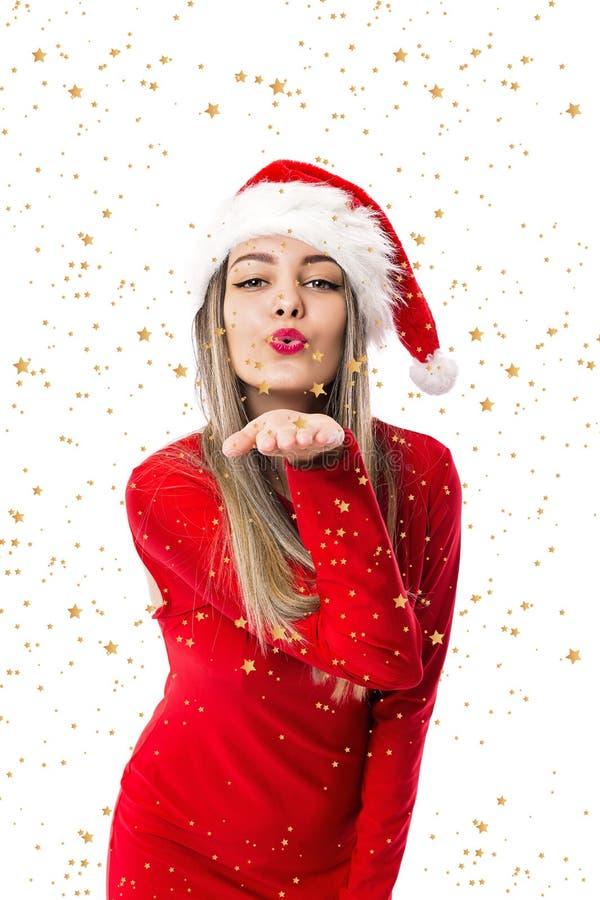 Portrait de belle femme utilisant le chapeau de Santa et soufflant des étoiles images libres de droits