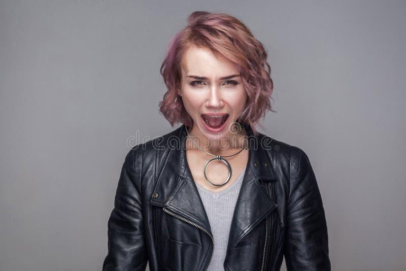 Portrait de belle fille agressive avec la coiffure et le maquillage courts dans la veste en cuir noire de style occasionnel se te photos stock