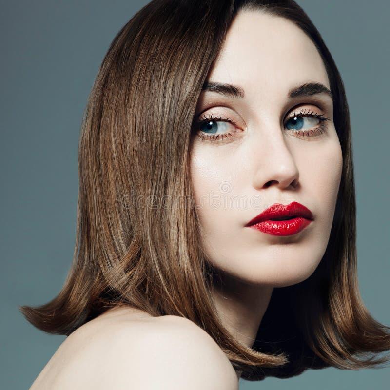 Portrait de belle fille avec le rouge à lèvres rouge dans le studio sur un fond gris photos libres de droits