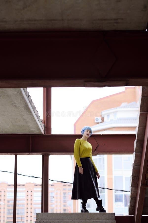 Portrait de belle fille avec les cheveux bleus et les lèvres rouges dans un chandail jaune au chantier de construction photographie stock