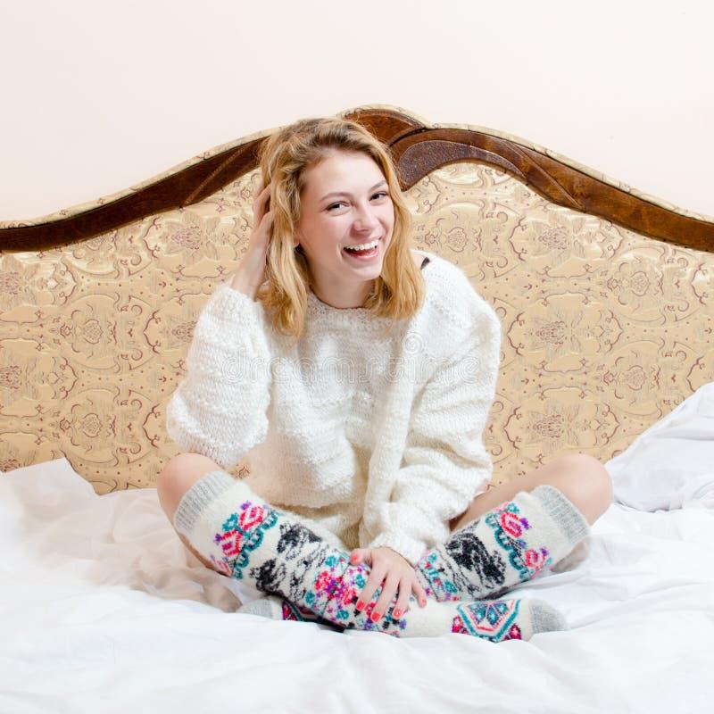 Portrait de belle fille blonde heureuse d'yeux bleus de jeune femme dans l'appareil-photo de regard tricoté et du sourire sur le  images libres de droits