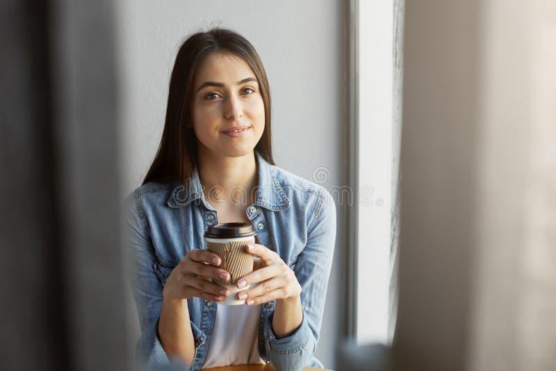 Portrait de belle fille décontractée avec les cheveux foncés dans le T-shirt blanc sous le regard de sourire de chemise de denim  image stock