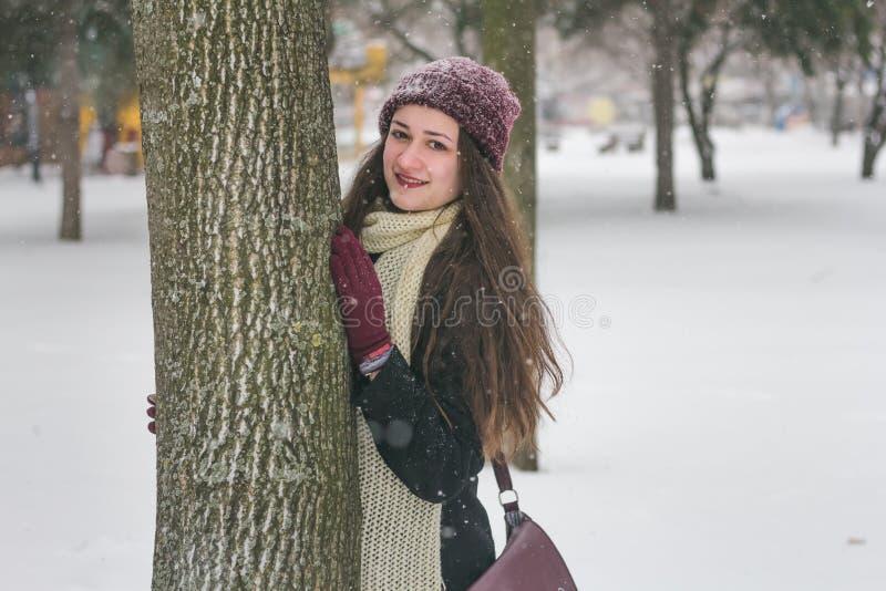 Portrait de belle fille dans la neige se cachant derrière un arbre photo stock