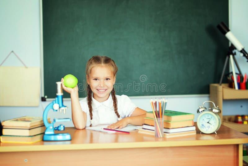 Portrait de belle fille dans la salle de classe au-dessus du tableau noir vert d'école photographie stock libre de droits