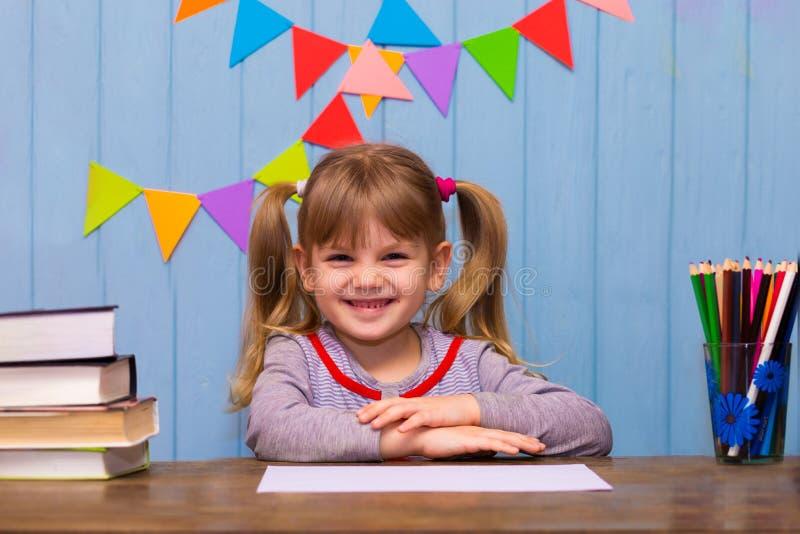 Portrait de belle fille dans la salle de classe Petite écolière s'asseyant au bureau et à l'étude photos stock