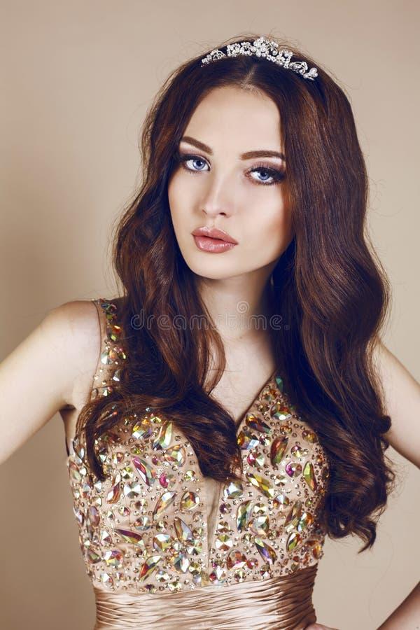 Portrait de belle fille de brune dans la robe et la couronne luxueuses de paillette image libre de droits