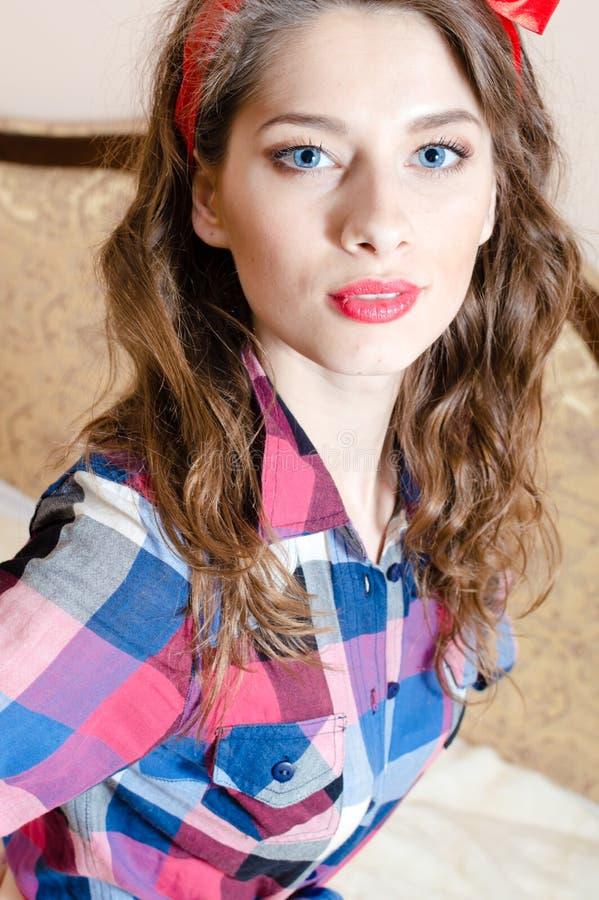 Portrait de belle fille de pin-up avec les yeux bleus et le rouge à lèvres rouge regardant l'appareil-photo posant dans le lit photo stock