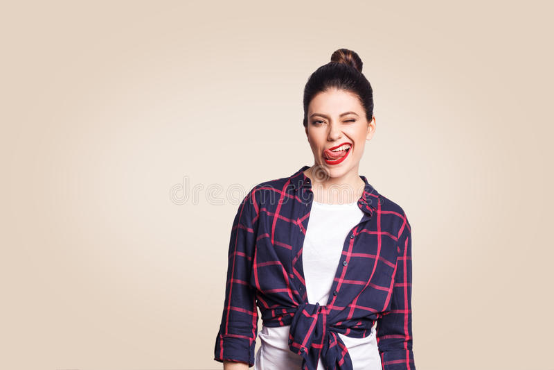 Portrait de belle fille heureuse dans le style occasionnel regardant l'appareil-photo avec le visage et la langue et le clin d'oe images libres de droits
