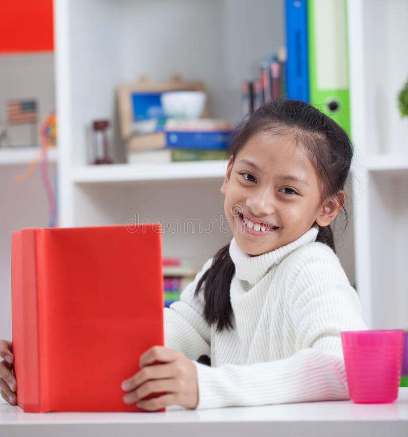 Portrait de belle fille lisant le grand livre dans la maison images stock